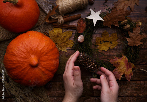 Children hands make autumn wreath on wooden table background Wallpaper Mural
