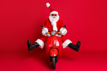 Full Length Photo Of Retired Grandfather White Beard Crazy Careless Ride Retro Moped Wind Blow Face High Speed Wear X-mas Costume Coat Sunglass Cap Boots Isolated Red Color Background