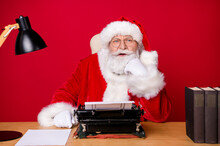 Photo Of Santa Claus Grey Beard Sit Desk Hand Cheekbone Think Vintage Typewriter Lamp Paper Book Wear X-mas Costume Coat Cap Glasses Isolated Red Color Background