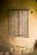 Vintage Wooden Window On Yellow Stone Wall.
