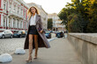 Fashion full length image of elegant  blond  woman in stylish luxury beige leather  coat and hight heels, walking  outdoor. Autumn fashion look.