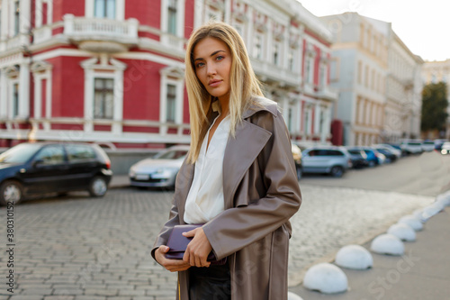 Obraz na plátně Lovely blond woman in autumn trendy outfit walking in the city