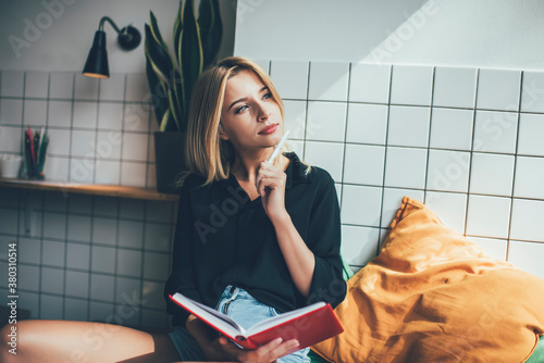 Fototapeta Contemplative hipster girl dressed in casual apparel holding education notepad f