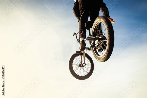 Urban biker performing acrobatic jump at sunny sky - Guy riding bmx bicycle at extreme sport competition on sunny afternoon - Alternative lifestyle concept on warm sunshine colors.