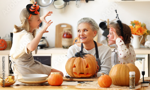 Cuadros en Lienzo Granddaughters scaring grandmother during Halloween celebration.