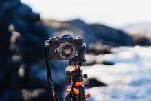 Black Unbranded Reflex Camera Planted On A Tripod Facing The Camera.