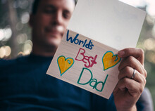 Father Holding A Homemade Card That Says World's Best Dad On Father's Day