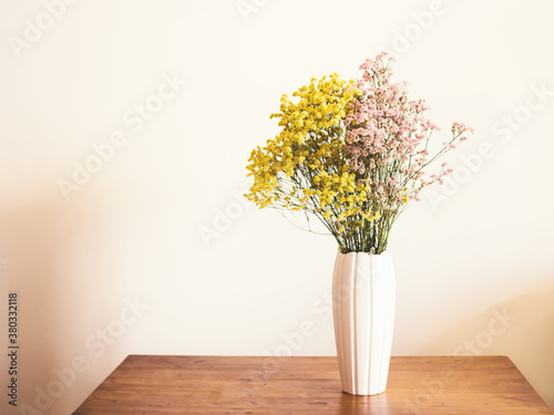 Dried pink and yellow flowers in white vase against white wall Canvas