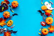 Frame of Halloween pumpkins, cookies and candies, top view
