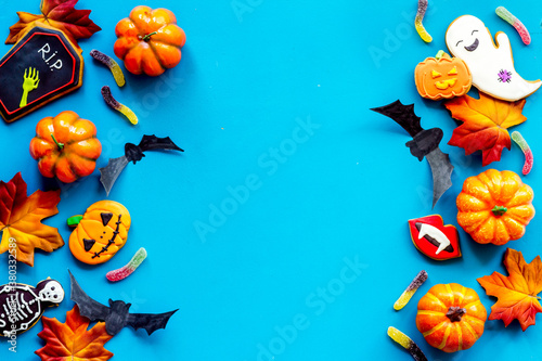 Frame of Halloween pumpkins, cookies and candies, top view