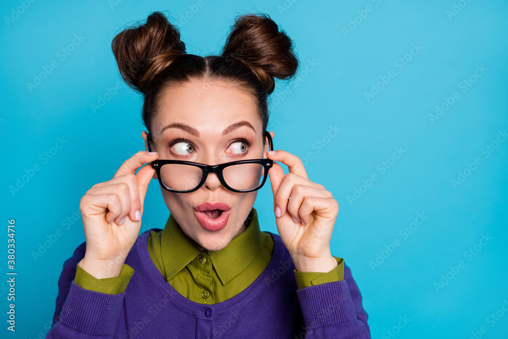 Fototapeta Closeup photo of attractive lady two funny buns good mood take off vision eyesight specs interested look side empty space wear shirt collar violet sweater isolated blue color background