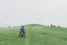 Man In Wheel Chair Climbing Steep Hill