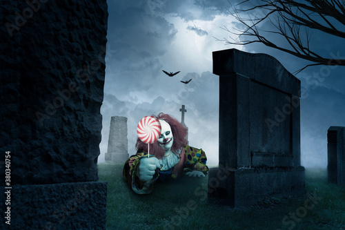 Fényképezés eerie clown with a lolly on a cemetery
