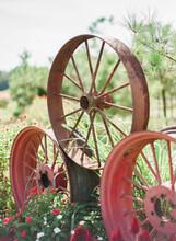 Three Old Rusted Wagon Wheels Displayed On A Farm
