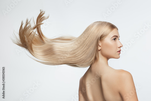 Fototapeta Beautiful model with long smooth, flying blonde hair isolated on white studio background
