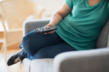 Woman Sitting On Sofa With Remote Control