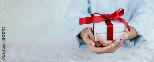 Woman hand in a blue shirt holding a white gift box tied with a red ribbon present for the festival of giving special holidays like Christmas, Valentine's Day