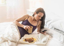 Woman Having Breakfast In Bed, Using Mobile Phone