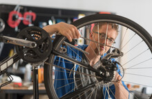 Man Repairing Bike In Shop