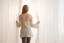 Young Woman Opening Curtains I...