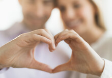 Couple Making Heart Shape With...