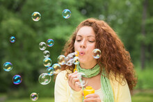 Young Woman Blowing Bubbles In...