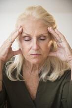 Portrait Of Senior Woman Holding Head, Eyes Closed