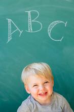 Boy (2-3) Smiling In Front Of Blackboard With Letters ABC Written On It
