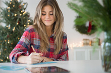 Young Woman Sitting At Table And Writing