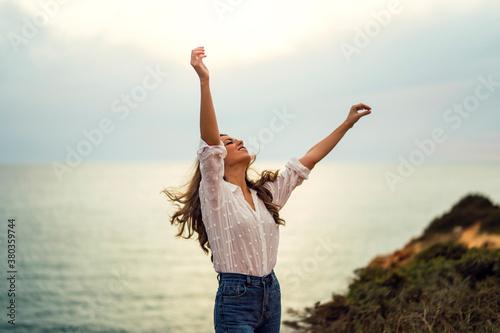 Chica con blusa blanca y bonita sonrisa en un acantilado Wallpaper Mural