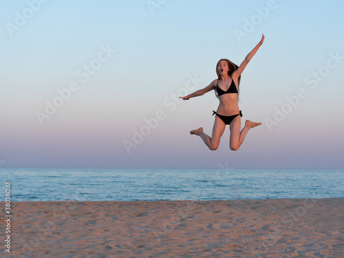 Fotografie, Obraz Girl jumping by the sea