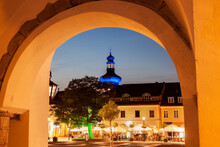 Illuminated Main Square With Sidewalk Cafe And Blue Onion Dome Seen Through Arch