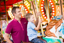 Father And Son (4-5) On Carousel In Amusement Park