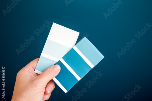 Close up view of person hand holding different blue color scheme and choosing a home wall paint Fotobehang
