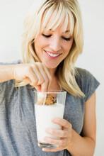 Studio Portrait Of Blonde Woman Dipping Cookie In Milk