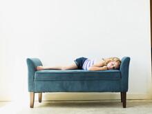 Girl (4-5) Sleeping On Bench Indoors