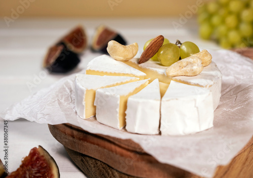 Camembert cheese on wooden board, branch of green grapes , slice of figs and nuts Fototapet