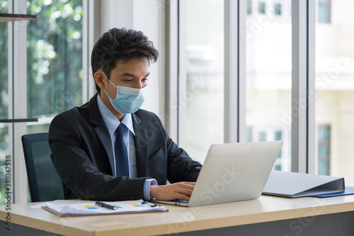 Fototapeta Young Asian businessmen wears a mask while working in the office. To protect himself from the spread of infectious coronavirus diseases 2019 obraz