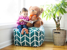 Girl (4-5) Sitting With Teddy Bear On Bean Bag
