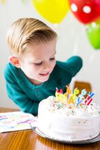 Boy (2-3) Looking At Birthday Cake
