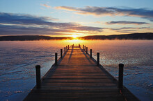 Symmetrical View Of Jetty On Frozen Lake, Hills In Background At Sunrise