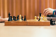 Hands Playing Chess On A Wooden Board
