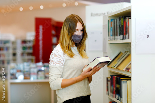 Fotografiet Young beautiful woman with medical mask in public library, choosing books for leisure or education