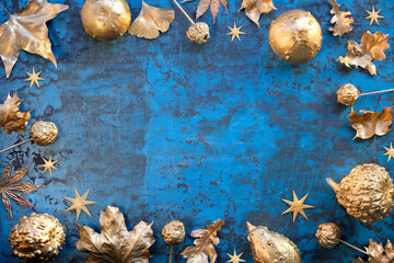 Obraz na płótnie Canvas Autumn frame in classic blue and metallic gold colored Fall leaves, pumpkins, fruits and stars, copy-space.