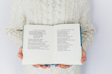 Child Holding A Book Of Christmas Songs