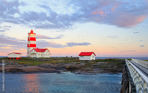 Pointe-des-Monts Lighthouse at sunset with reflections in the sea, Cote-Nord, Quebec