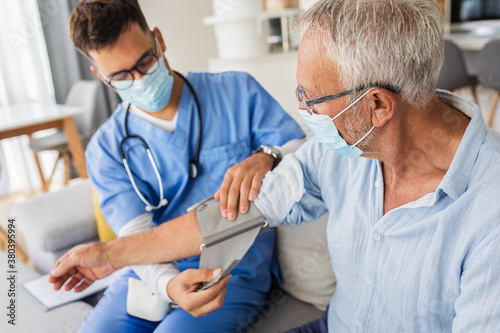 Male nurse measures blood pressure to senior man with mask while being in a home visit Fototapet
