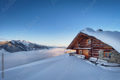 Cuadros en Lienzo Snow covered mountain hut old farmhouse in the Austrian alps at sunrise against blue sky
