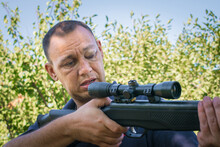 A Man With A Damaged Eye Holds A Rifle In His Hands. The Guy Tries To Aim At The Telescopic Sight. Bad Shot