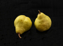 Two Yellow Pears On Black Background